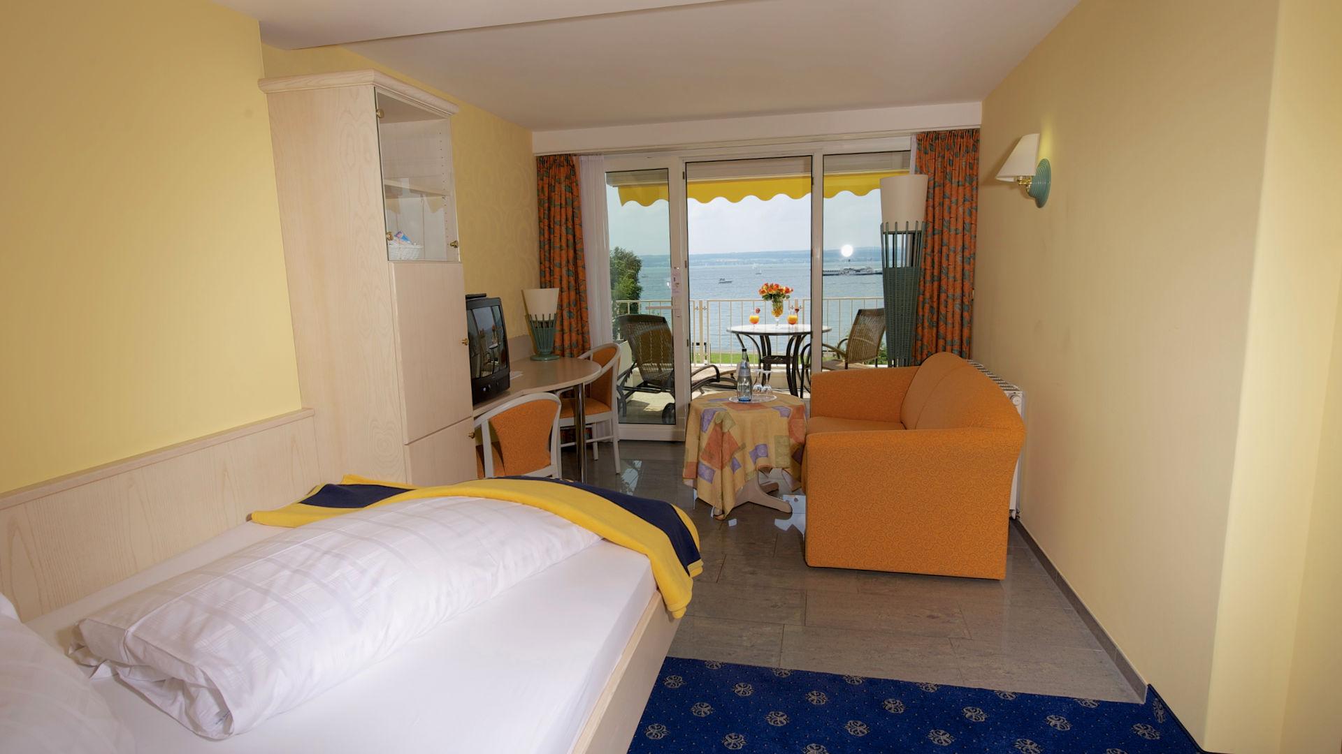 Blick auf Zimmer und See Einzelzimmer mit Wohnbereich, Balkon und Seeblick